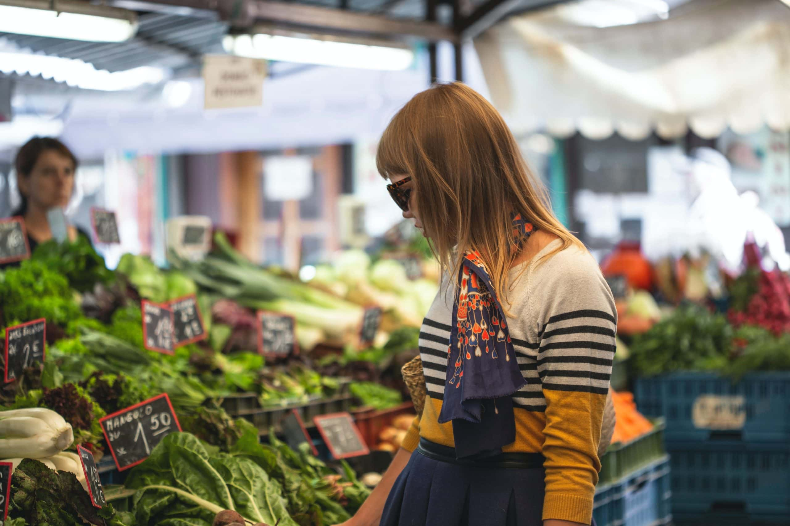 woman standing in front of vegetables in market during day time